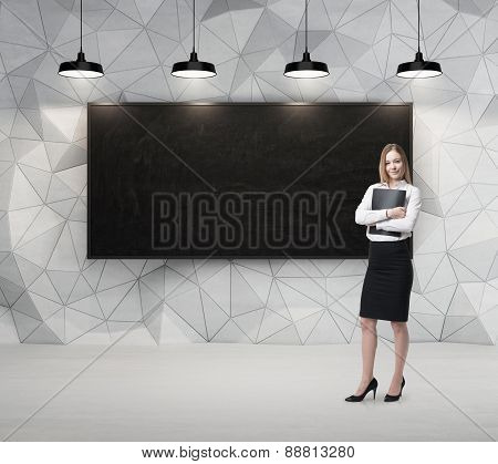 Young Beautiful Business Lady Is Holding A Black Document Case. Blank Blackboard On The Background.