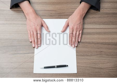 Close Up Of Businesswoman's Hands On The Desk With The Blank Paper. Legal Contract Negotiation.