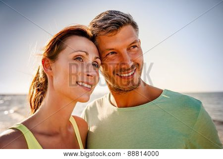 smiling younger couple after workout on the sea