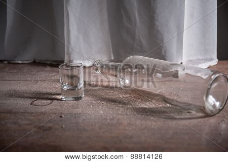 Bottle And Glass On The Dirty Floor