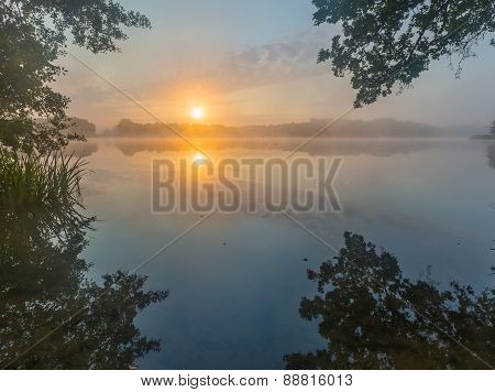Beautiful Sunrise Over Misty Lake.