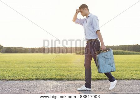 Full length of tired young man with gas can walking on rural road