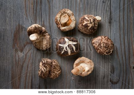 Dried shiitake mushrooms on wooden background.