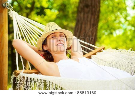 Happy Woman Relaxing in a Hammock