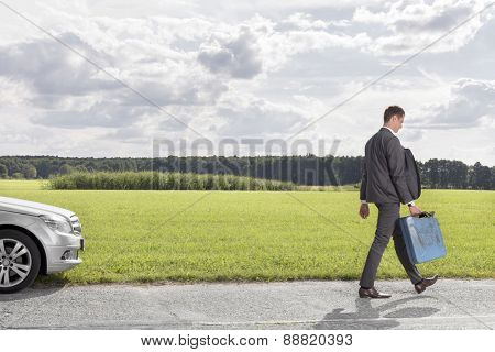 Full length of young businessman with gas can leaving broken down car at countryside