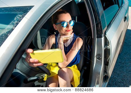 Woman making self portrait in the car