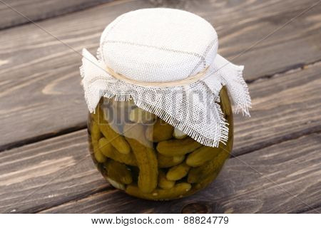Pickled cucumbers in jar on wooden table