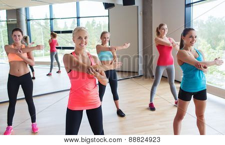 fitness, sport, training, gym and lifestyle concept - group of happy women working out and stretching shoulder in gym