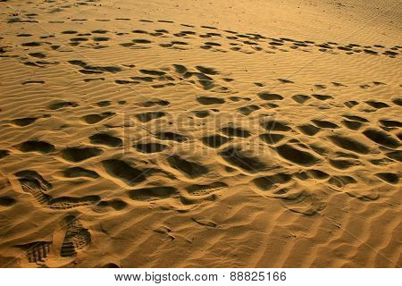 Footprints On Sand At Sunset