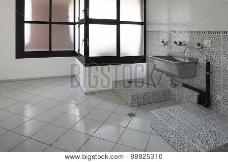 Interior house, empty laundry, gray tiled floor