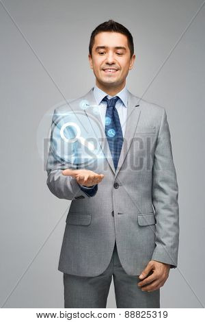 business, people, search and technology concept - happy businessman in suit showing or holding virtual projection of computer settings on hand palm