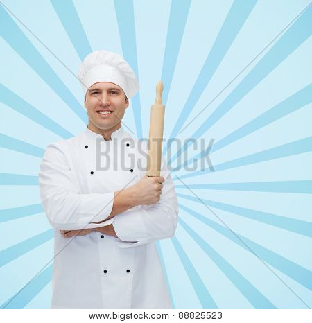cooking, profession and people concept - happy male chef cook holding rolling pin over blue burst rays background