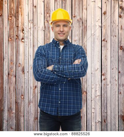 repair, construction, building, people and maintenance concept - smiling male builder or manual worker in helmet over wooden fence background