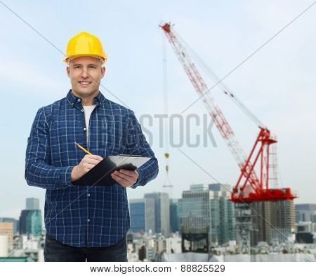 repair, construction, building, people and maintenance concept - smiling male builder or manual worker in helmet with clipboard taking notes over city construction site background