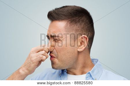 emotions, gesture and people concept - man wrying of unpleasant smell and closing his nose over gray background