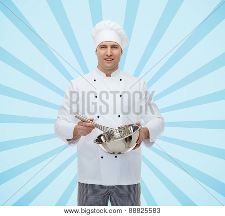 cooking, profession and people concept - happy male chef cook holding bowl and whipping something with whisk over blue burst rays background