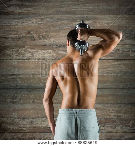 sport, fitness, weightlifting, bodybuilding and people concept - young man with dumbbell flexing biceps over wooden wall background from back