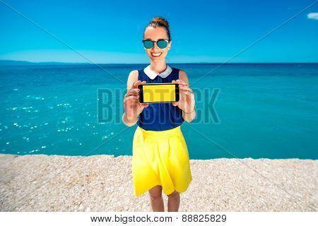 Woman showing phone screen near the sea