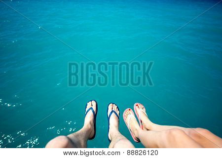 Couple's legs in slippers on the sea background