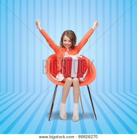 people, christmas, holidays, presents and childhood concept - happy little girl with gift boxes sitting and raised arms on chair over blue striped background