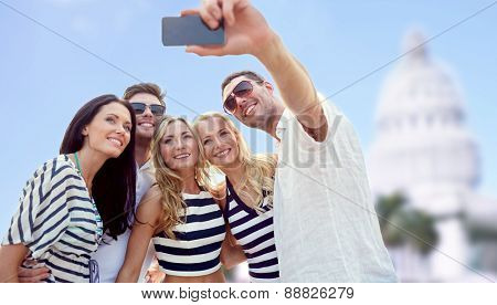summer, tourism, technology and people concept - group of smiling friends taking selfie with smartphone over american white house background