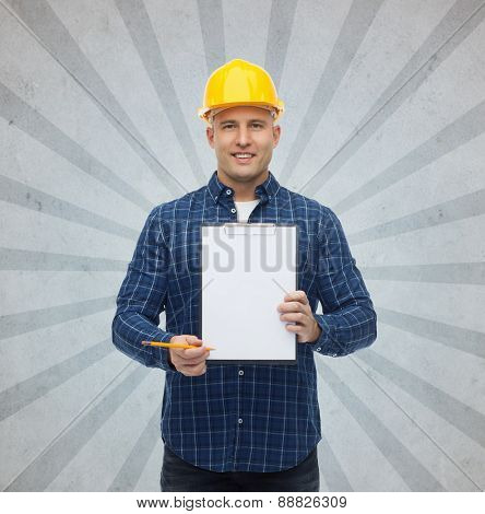 repair, construction, building, people and maintenance concept - smiling male builder or manual worker in helmet with clipboard over gray burst rays background