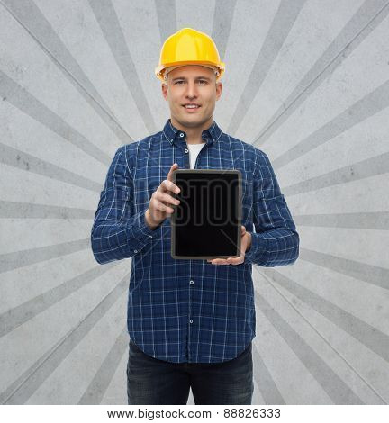 repair, construction, building, people and maintenance concept - smiling male builder or manual worker in helmet showing tablet pc computer blank screen over gray burst rays background