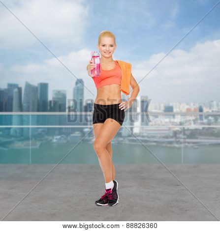 sport, fitness, healthy lifestyle and people concept - sporty woman with orange towel and water bottle over city waterside background