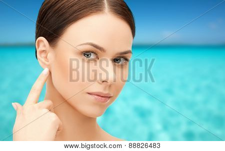 people, beauty, hearing and healthcare concept - face of beautiful woman touching her ear over blue sea and sky background
