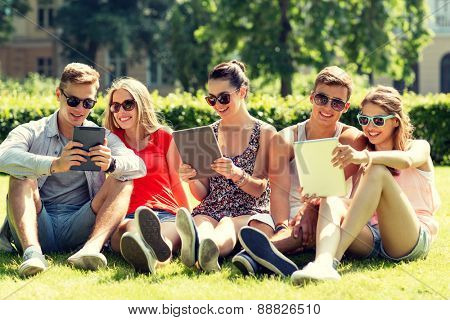 friendship, leisure, summer, technology and people concept - group of smiling friends with tablet pc computers sitting on grass in park