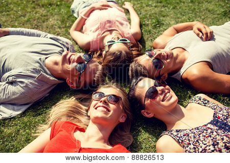 friendship, leisure, summer and people concept - group of smiling friends lying on grass in circle outdoors