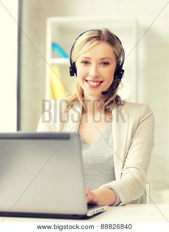smiling female helpline operator with headphones and laptop