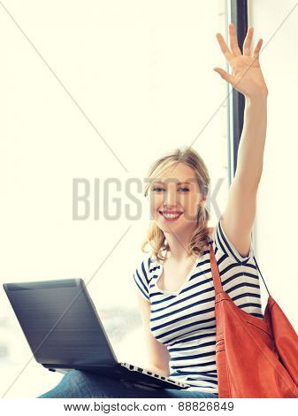happy teenage girl waving a greeting with laptop