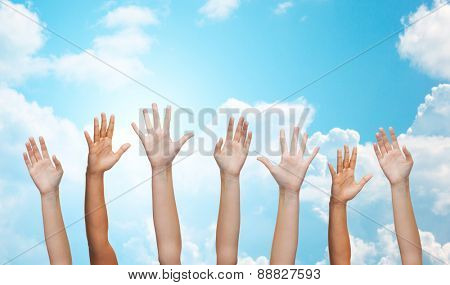 gesture, greeting, charity and body parts concept - people waving hands over blue sky and white clouds background