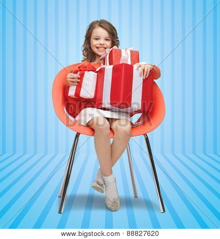 people, christmas, holidays, presents and childhood concept - happy little girl with gift boxes sitting on chair over blue striped background