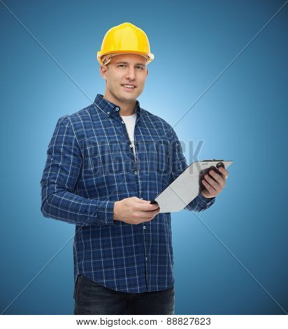 repair, construction, building, people and maintenance concept - smiling male builder or manual worker in helmet with clipboard over blue background