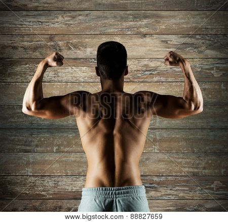 sport, fitness, bodybuilding, strength and people concept - young man or bodybuilder showing biceps over wooden wall background from back
