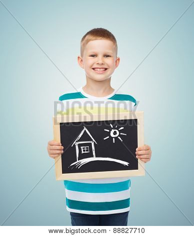 education, creativity, drawing and children concept - smiling little boy holding black chalk board with picture of home over blue background