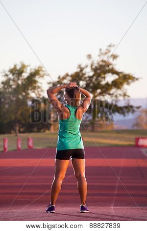 Close up wide angle view of a female sprinter athlete getting ready to start a race on a tartan racetrack with dramatic lighting late in the afternoon, just before dusk.