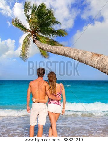 Couple of young tourists in a tropical summer beach with coconut palm trees