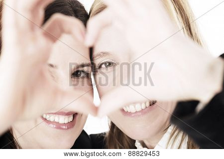 Two happy business women with heart