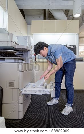 Young Woman Inserting Pwoman inserting paper in laser printer cartridge