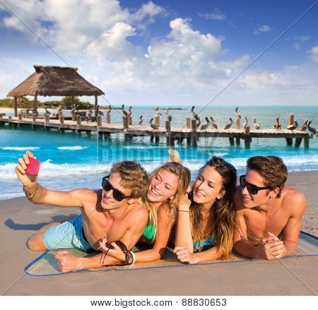Selfie photo of young friends group in a tropical beach lying on sand