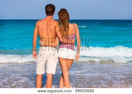 Couple of young tourists in a tropical summer beach rear view hug