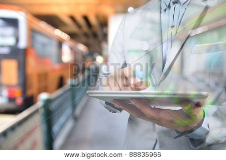Business Man Using Mobile Digital Tablet In Bus Station