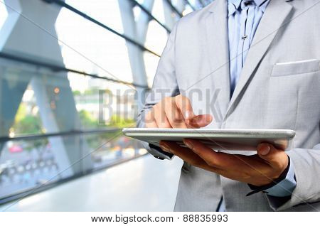 Handsome Young Business Man In Office Building Using Digital Mobile Tablet.