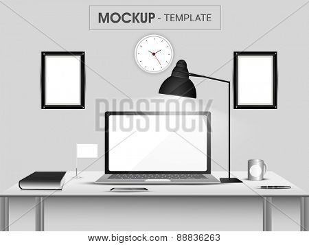 Stylish workspace with laptop, smartphone, book, coffee mug, frame and clock on grey background.
