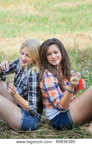 Blonde and brunette girls playing with iridescent soap bubbles