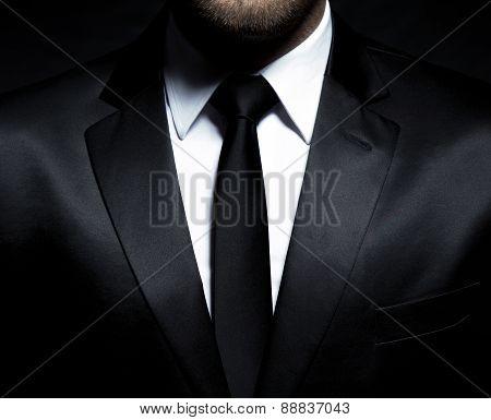 Gentleman wearing a black suit, shirt and tie, tuxedo