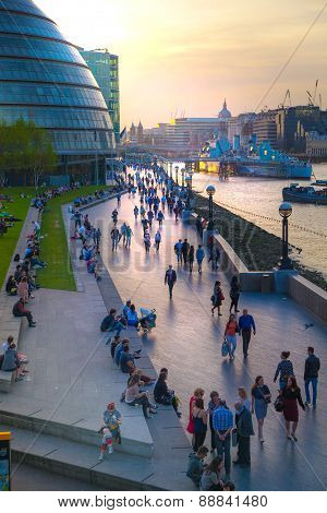 LONDON, UK - APRIL15, 2015: South walk of river Thames in sun set light. View includes a lot of walk